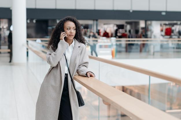 Mujer joven con un smartphone de pie de pie en el pasillo del centro comercial