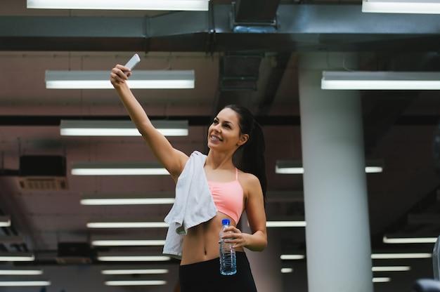 Mujer joven con smartphone tomando selfie en gimnasio