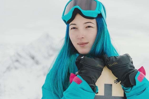 Mujer joven con snowboard en invierno