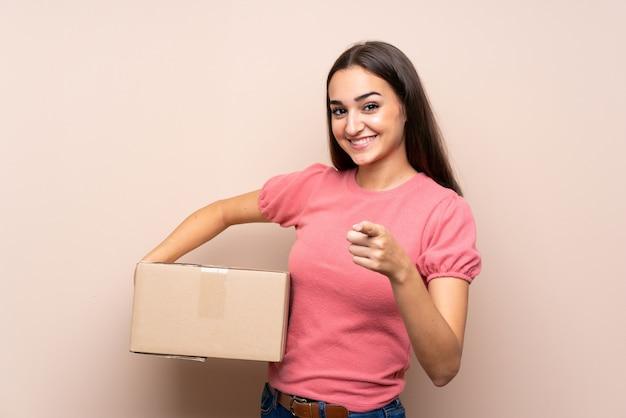 Mujer joven sobre aislada sosteniendo una caja para moverla a otro sitio mientras apunta hacia el frente
