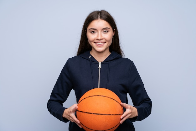Mujer joven sobre aislado con pelota de baloncesto