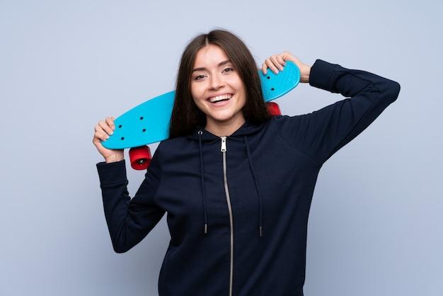 Mujer joven sobre aislado con skate