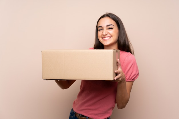 Mujer joven sobre aislado sosteniendo una caja para moverlo a otro sitio