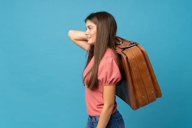 Mujer joven sobre azul aislado sosteniendo un maletín vintage