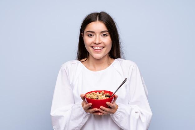 Mujer joven sobre azul aislado sosteniendo un tazón de cereales