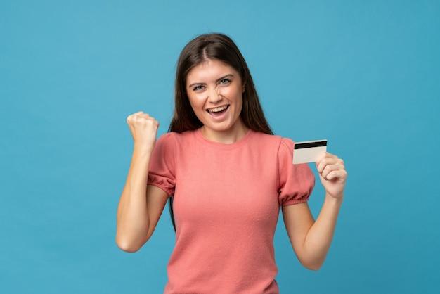 Mujer joven sobre azul aislado con una tarjeta de crédito