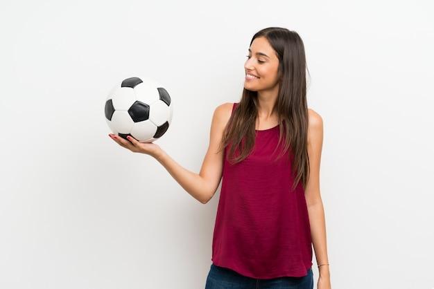 Mujer joven sobre blanco aislado que sostiene un balón de fútbol