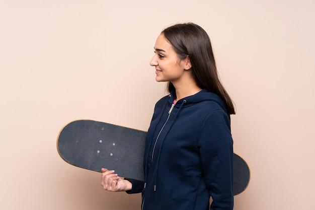 Mujer joven sobre fondo aislado con patines en posición lateral
