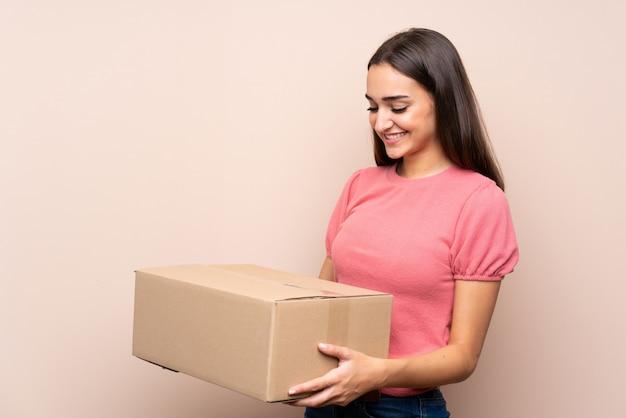 Mujer joven sobre fondo aislado sosteniendo una caja para moverlo a otro sitio