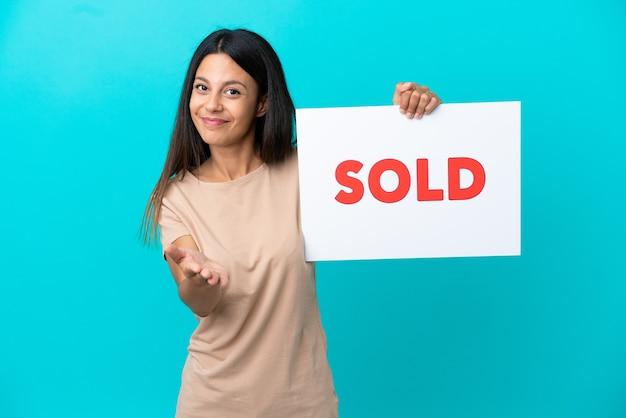 Mujer joven sobre fondo aislado sosteniendo un cartel con texto vendido haciendo un trato