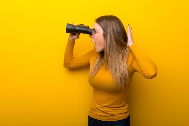 Mujer joven sobre fondo amarillo y mirando en la distancia con binoculares