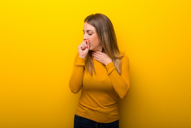 Mujer joven sobre fondo amarillo sufre de tos y se siente mal