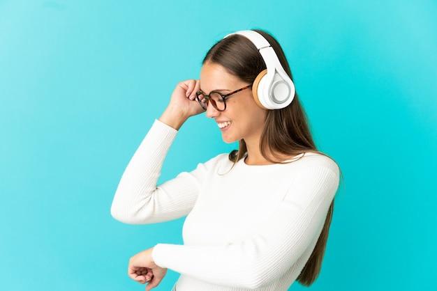 Mujer joven sobre fondo azul aislado escuchando música y bailando