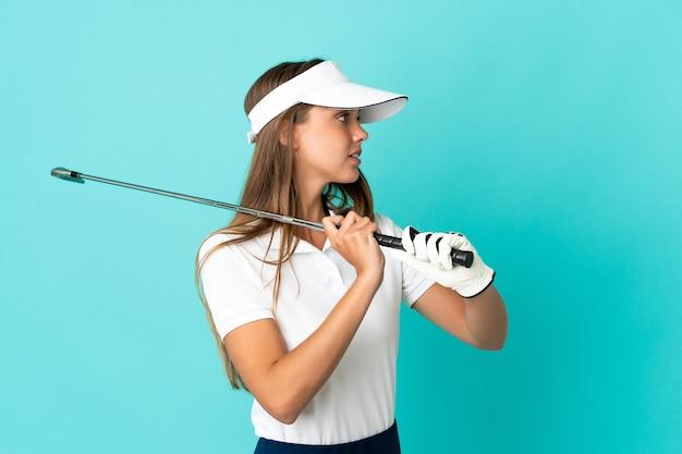 Mujer joven sobre fondo azul aislado jugando al golf