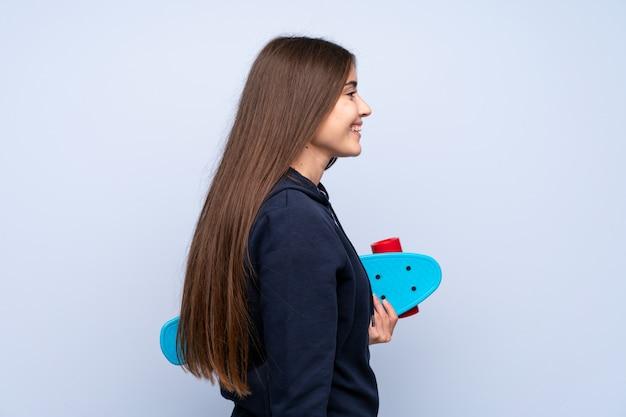 Mujer joven sobre fondo azul aislado con patines en posición lateral