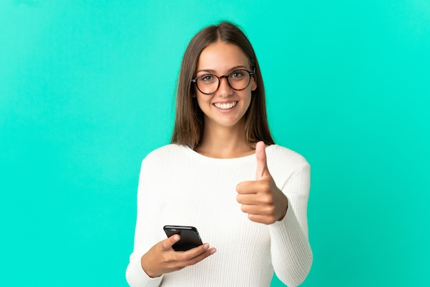 Mujer joven sobre fondo azul aislado mediante teléfono móvil mientras hace thumbs up