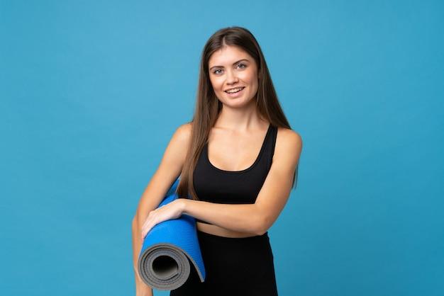 Mujer joven sobre pared aislada con una estera y sonriente