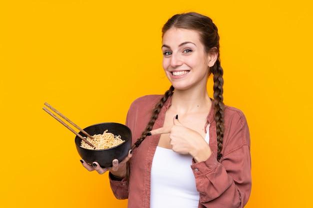Mujer joven sobre pared amarilla aislada y apuntando mientras sostiene un tazón de fideos con palillos