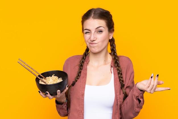 Mujer joven sobre pared amarilla aislada haciendo dudas gesto mientras levanta los hombros mientras sostiene un tazón de fideos con palillos
