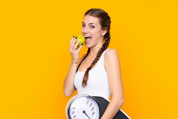 Mujer joven sobre pared amarilla aislada con máquina de pesaje y con una manzana