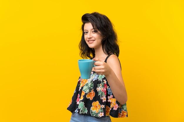 Mujer joven sobre la pared amarilla aislada que sostiene la taza de café caliente