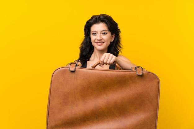 Mujer joven sobre pared amarilla aislada sosteniendo un maletín vintage