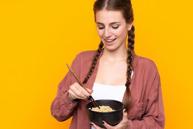 Mujer joven sobre pared amarilla aislada sosteniendo un tazón de fideos con palillos