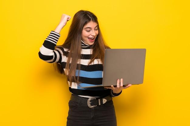 Mujer joven sobre pared amarilla con laptop y celebrando una victoria