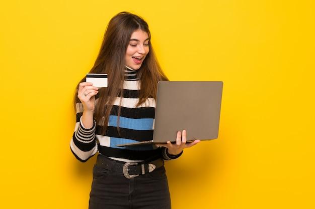 Mujer joven sobre pared amarilla con laptop y tarjeta de crédito