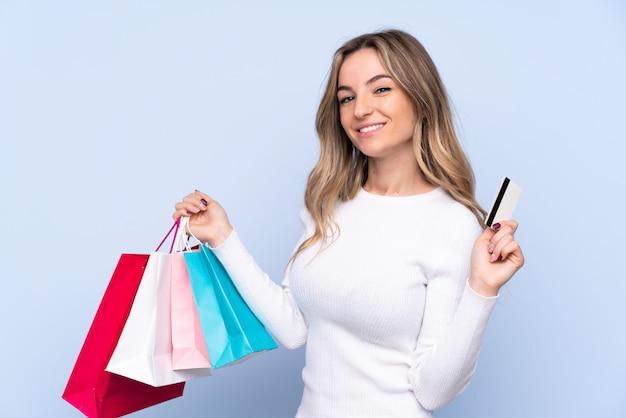 Mujer joven sobre pared azul aislada con bolsas de compras y una tarjeta de crédito