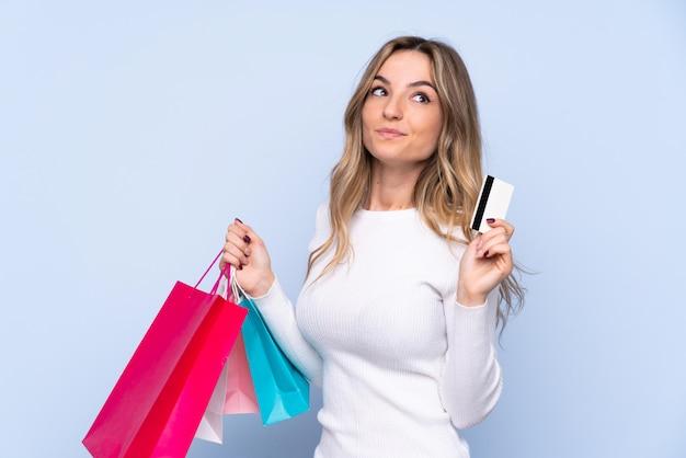Mujer joven sobre pared azul aislada sosteniendo bolsas de compras y una tarjeta de crédito y pensando