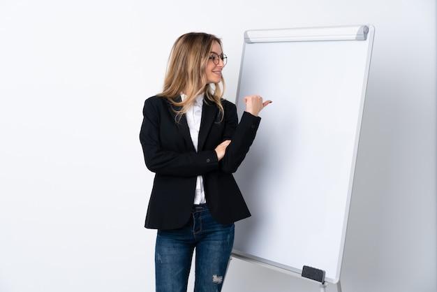 Mujer joven sobre pared blanca aislada apuntando hacia un lado para presentar un producto