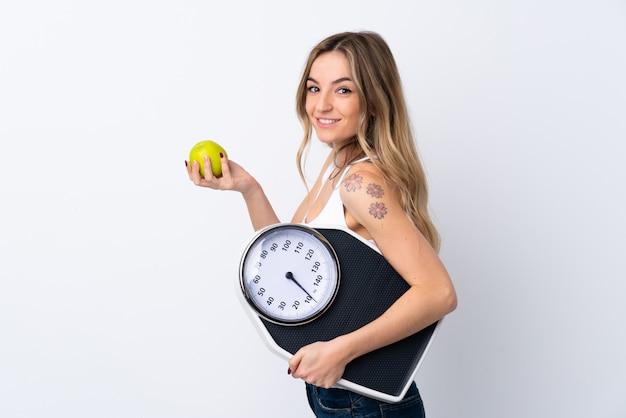 Mujer joven sobre pared blanca aislada con máquina de pesaje y con una manzana