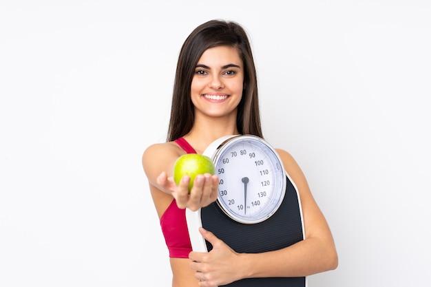 Mujer joven sobre la pared blanca aislada que sostiene la máquina de pesaje y que ofrece una manzana