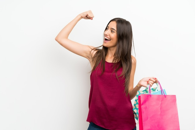 Mujer joven sobre la pared blanca aislada que sostiene muchas bolsas de compras