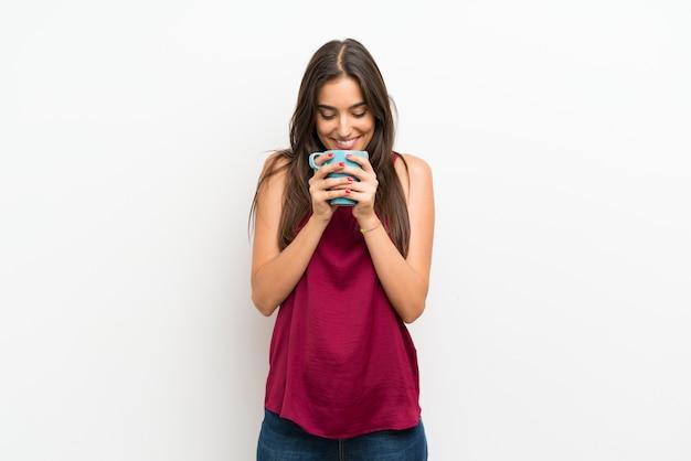 Mujer joven sobre la pared blanca aislada que sostiene la taza de café caliente