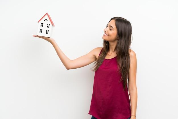 Mujer joven sobre pared blanca aislada sosteniendo una casita
