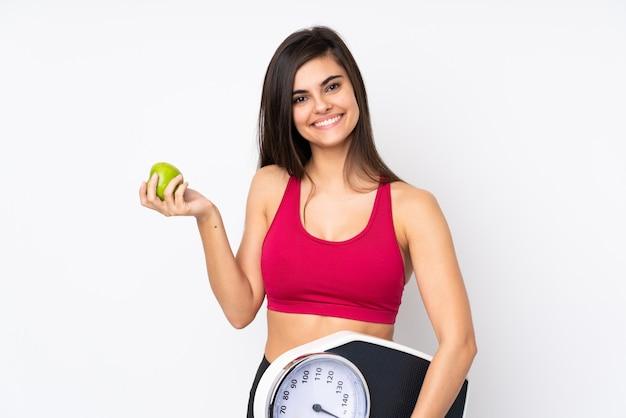Mujer joven sobre pared blanca con máquina de pesaje y con una manzana