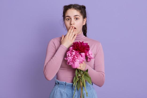 Mujer joven sobre pared lila con atuendos casuales doblando flores en las manos, sorprendida, cubriendo la boca con la mano por error, posando contra la pared lila.