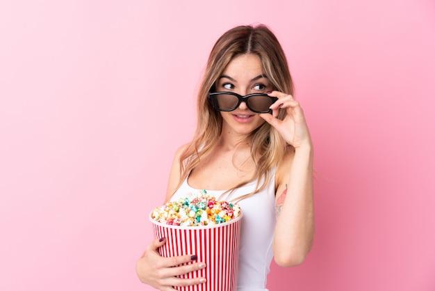 Mujer joven sobre pared rosa aislada con gafas 3d y sosteniendo un gran cubo de palomitas de maíz