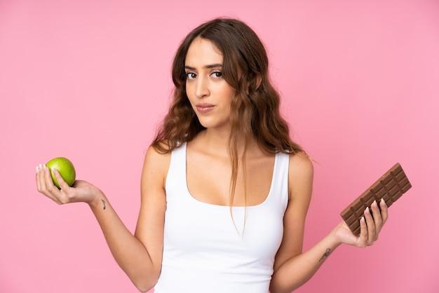 Mujer joven sobre pared rosa aislada que tiene dudas mientras toma una tableta de chocolate en una mano y una manzana en la otra