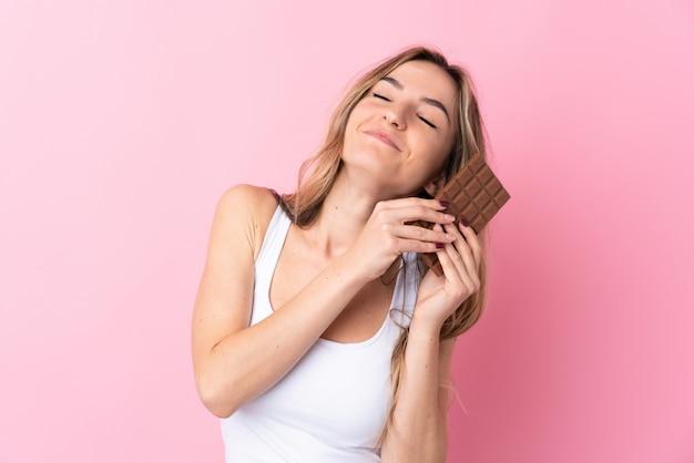 Mujer joven sobre pared rosa aislada tomando una tableta de chocolate y feliz