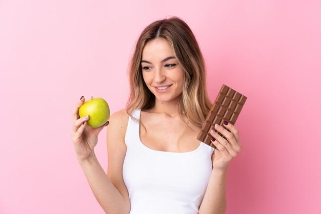 Mujer joven sobre pared rosa aislada tomando una tableta de chocolate en una mano y una manzana en la otra