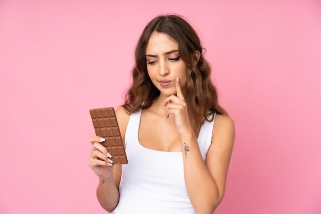 Mujer joven sobre pared rosa aislada tomando una tableta de chocolate y teniendo dudas