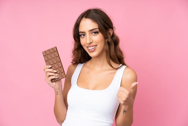 Mujer joven sobre pared rosa aislado tomando una tableta de chocolate y con el pulgar hacia arriba