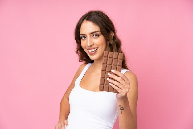 Mujer joven sobre pared rosa tomando una tableta de chocolate y feliz
