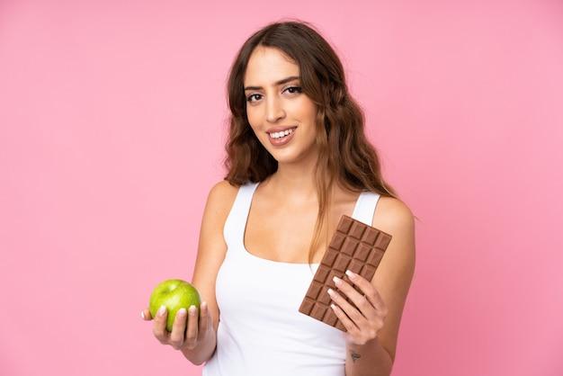 Mujer joven sobre pared rosa tomando una tableta de chocolate en una mano y una manzana en la otra