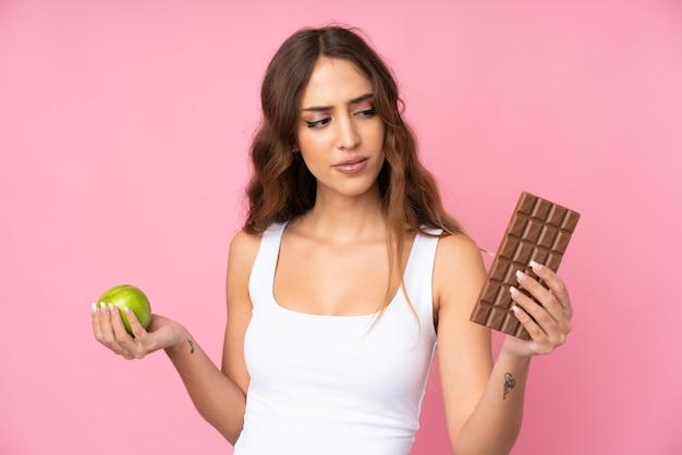 Mujer joven sobre pared rosada que tiene dudas mientras toma una tableta de chocolate en una mano y una manzana en la otra