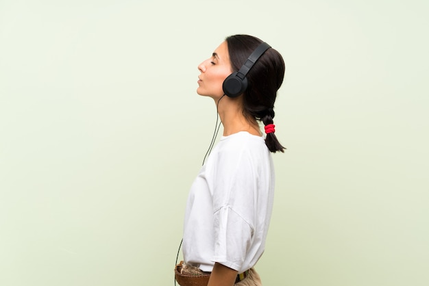 Mujer joven sobre pared verde aislada escuchando música con auriculares