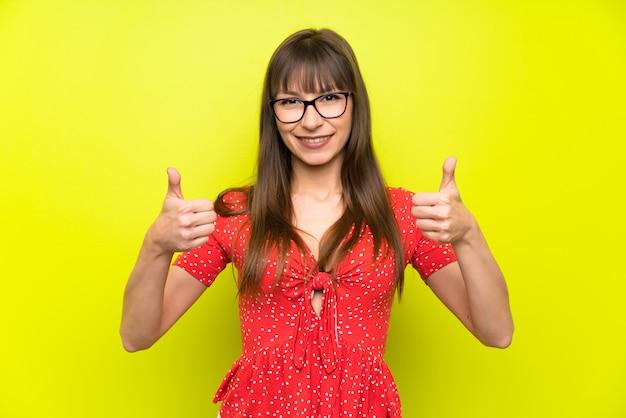 Mujer joven sobre la pared verde que da un pulgares arriba gesto